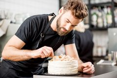 Confectioner decorating a pie royalty free stock photo