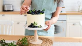 Confectioner decorating wedding cake with berries. Close up. White cake with cream cheese and fresh blueberries and blackberries. stock images