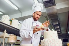 A confectioner with dessert in his hands. A confectioner with dessert in his hands in the bakery.r royalty free stock photo