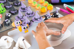 Confectioner with figures of halloween. Confectioner working on the figures of Halloween with fondant paste Royalty Free Stock Photo