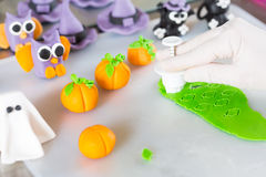 Confectioner with figures of halloween. Confectioner working on the figures of Halloween with fondant paste Royalty Free Stock Photography
