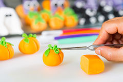 Confectioner with figures of halloween. Confectioner working on the figures of Halloween with fondant paste Stock Photo