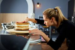 The confectioner girl puts the cakes for the cake. Stock Photography