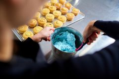 The confectioner makes a cream for cupcakes on a kitchen table. Royalty Free Stock Photography