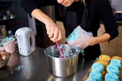 The confectioner makes a cream for cupcakes on a kitchen table. Stock Photography