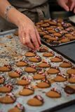 Confectioner making cookies, tea pastes, dipped in chocolate and decorated with sugar hearts stock photos