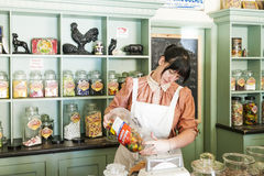 Confectioner Old Sweet Shop, Blists Hill Victorian Town. Ironbridge, Telford, England- July 9, 2014. Young woman weighs out candy (midjet gums) for a customer at Royalty Free Stock Image