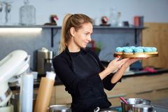 Confectioner pastry woman holding a tray of cupcakes. Stock Images