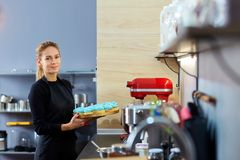 Confectioner woman holding a tray of cupcakes. Royalty Free Stock Images