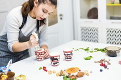 A confectioner prepares a trifle in three cups. Desserts are on the white table in the kitchen. The concept of homemade royalty free stock image