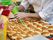 Confectioner is preparing bun with cream Royalty Free Stock Image