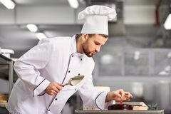 The confectioner is preparing a cake in the kitchen of the pastr Royalty Free Stock Images