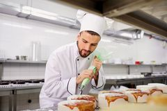 The confectioner is preparing a cake in the kitchen of the pastr Royalty Free Stock Image