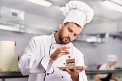 The confectioner is preparing a cake in the kitchen of the pastr Stock Image