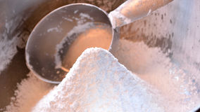 Confectioner's sugar widescreen with measuing cup. Closeup panorama photo of a mound of freshly sifted confectioner's sugar in stainless steel bowl with 1 cup Royalty Free Stock Photography