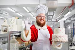 Confectioner Santa Claus with a cake in his hands for Christmas. Stock Photos