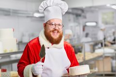 Confectioner Santa Claus with a cake in his hands for Christmas. Royalty Free Stock Photography