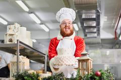 Confectioner Santa Claus with a cake in his hands for Christmas. Stock Photo