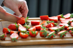 Confectioner sliced strawberries for garnishing the cake Stock Image