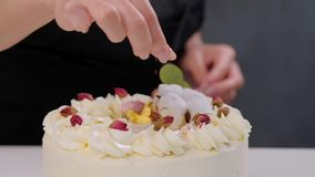 The confectioner sprinkles the cake with grated almonds and coconut. Close-up of a hand and pouring crumbs. stock video footage