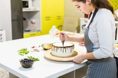 A confectioner squeezes liquid chocolate from a pastry bag onto a white cream biscuit cake on a wooden stand. The royalty free stock images
