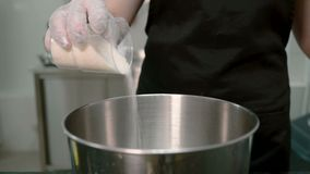 The confectioner is strewing the sugar from the plastic glass into the steel pot. stock footage