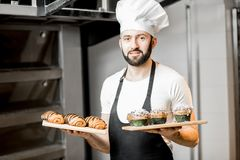 Confectioner with sweet pastry in the manufacturing stock images