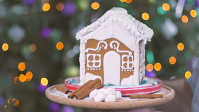 Confectioner turn the tray with gingerbread house. Close-up. Camera focuses on a tray with sweet gingerbread house, cinnamon and marshmallows. Human hands is stock footage