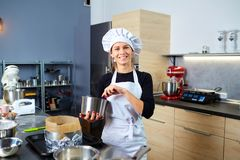 A confectioner woman with a cake in her hand in pastry shop. Stock Images