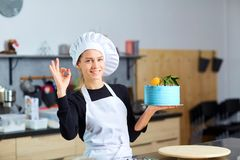 A confectioner woman with a cake in her hands in the kitchen. Royalty Free Stock Image
