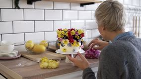 Confectioner woman decorates cake with flowers for holiday. Professional female chef makes a wedding or birthday cake. With fresh, eatable flowers. Slow motion stock video footage