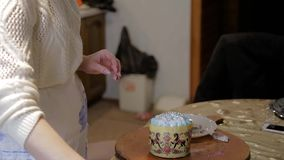 Confectioner woman and girl prepare Easter cakes and decorate them with colorful decor, woman prepares cakes in her own. HD Confectioner woman and girl prepare stock footage