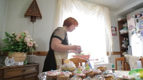 Confectioner woman and girl prepare Easter cakes and decorate them with colorful decor, woman prepares cakes in her own. HD Confectioner woman and girl prepare stock video