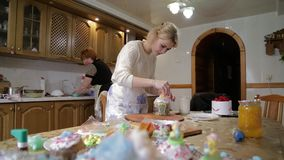 Confectioner woman and girl prepare Easter cakes and decorate them with colorful decor, woman prepares cakes in her own stock video
