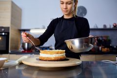A confectioner woman makes  cake in the kitchen. A confectioner woman makes  cake in the kitchen in a pastry shop Stock Photo