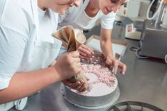 Confectioner women putting cream on cake Royalty Free Stock Photo