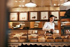 confectionery Πωλώντας καραμέλες σοκολάτας γυναικών στο κατάστημα στοκ φωτογραφία με δικαίωμα ελεύθερης χρήσης