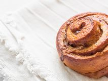 Confectionery baking. Sweet fresh soft roll bun with cinnamon on white background. Cinnabon closeup.  stock photo