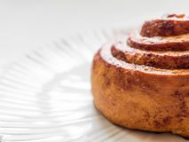 Confectionery baking. Sweet fresh soft roll bun with cinnamon on white background. Cinnabon closeup.  stock photography