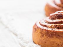 Confectionery baking. Sweet fresh soft roll bun with cinnamon on white background. Cinnabon closeup.  royalty free stock image