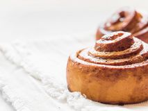 Confectionery baking. Sweet fresh soft roll bun with cinnamon on white background. Cinnabon closeup.  royalty free stock photos