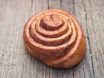 Confectionery baking. Sweet fresh soft roll bun with cinnamon on wooden background. Cinnabon closeup.  stock photo