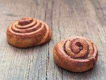 Confectionery baking. Sweet fresh soft roll bun with cinnamon on wooden background. Cinnabon closeup.  royalty free stock photo