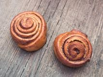 Confectionery baking. Sweet fresh soft roll bun with cinnamon on wooden background. Cinnabon closeup.  royalty free stock photography