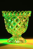 Confectionery Bowl of cut Glass. Confectionery bowl made of cut glass which reflets and refracts the green and yellow light from behind in many directions Royalty Free Stock Images