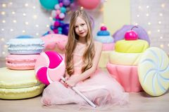 Confectionery concept - little girl with huge sweets and pastry decorations stock photos