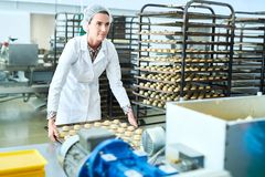 Confectionery factory employee holding tray with uncooked pastry. Confectionery factory worker in white coat standing holding baking sheet with raw pastry and stock photo