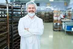 Confectionery factory employee standing and smiling. Confectionery factory worker standing in white coat with arms crossed smiling and looking at camera stock photo