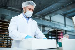 Confectionery factory employee preparing package. Confectionery factory employee standing in white coat and preparing paper package box stock image