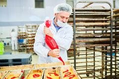 Confectionery factory employee using icing bag. Concentrated confectionery factory worker in white coat squeezing red cream from icing bag stock photo